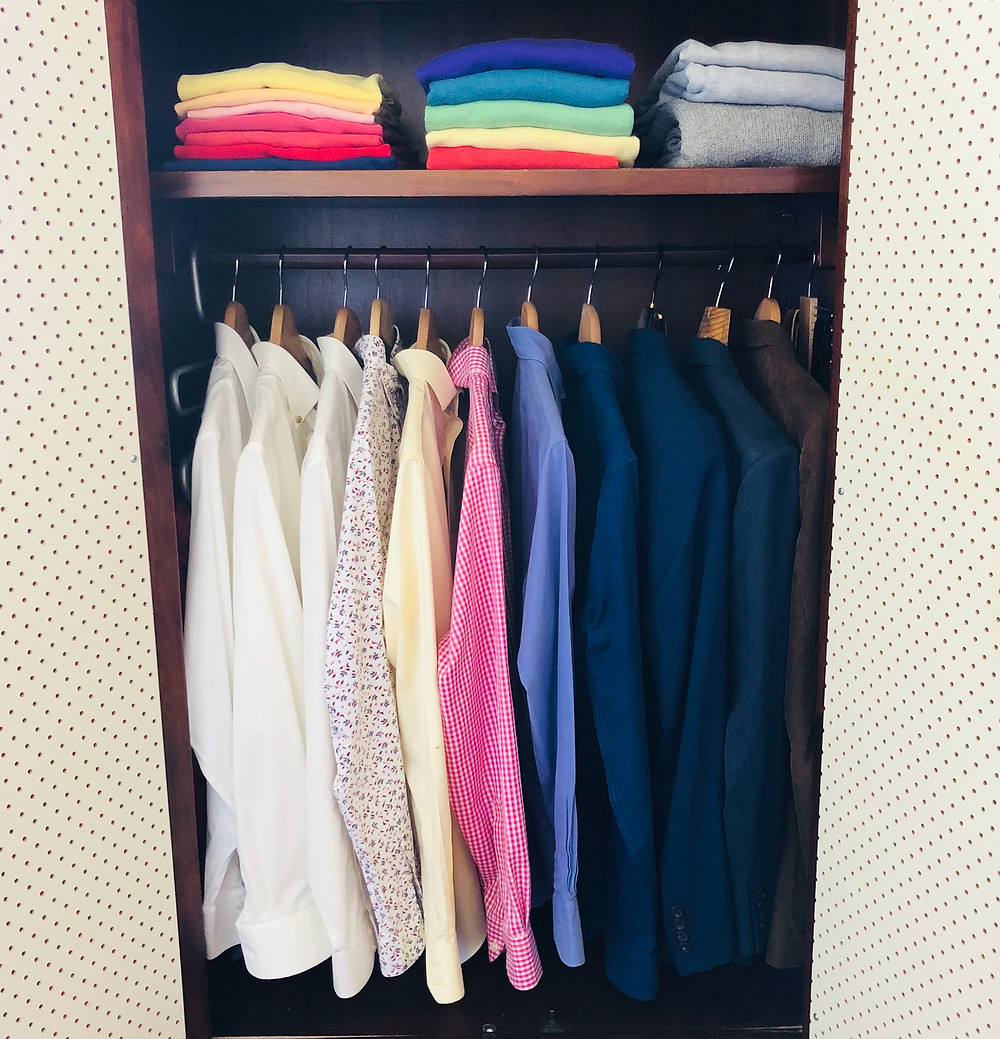 decluttered and organised wardrobe with shirts and folded sweaters
