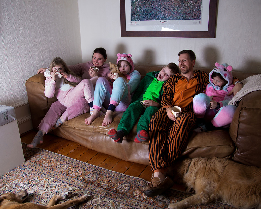 Family of 6 on a sofa to watch a movie.