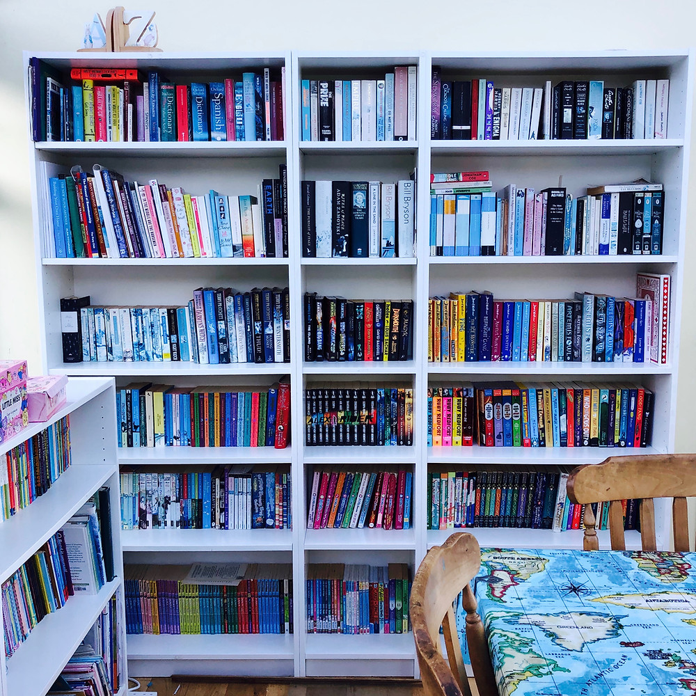 An organised bookshelf, full of books.