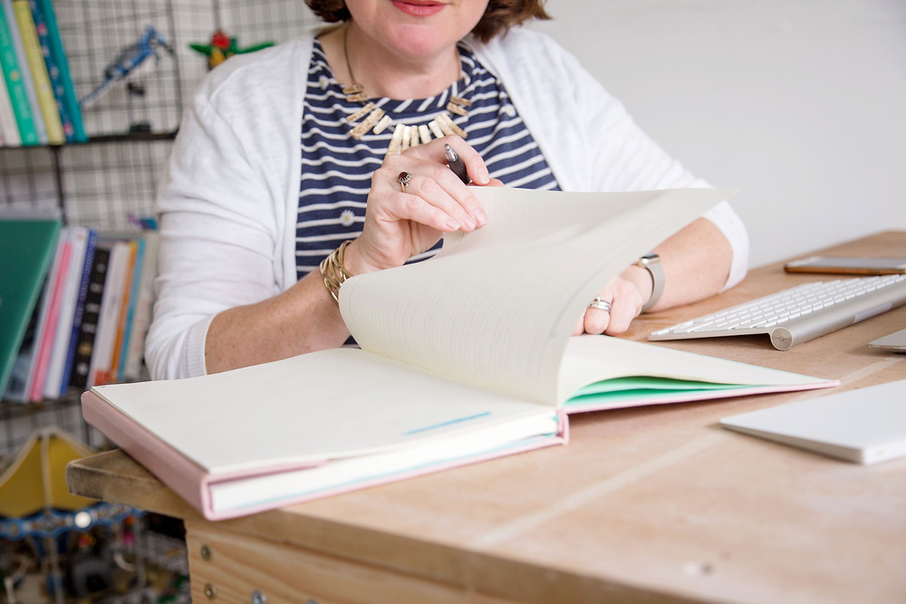picture shows woman turning page of notebook