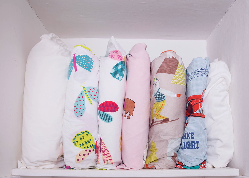 Sheets folded into pillow cases and stacked vertically on shelves for easy access.