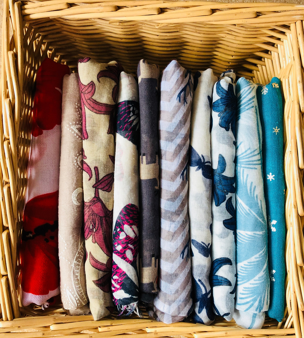 Scarves organised and folded into a basket.