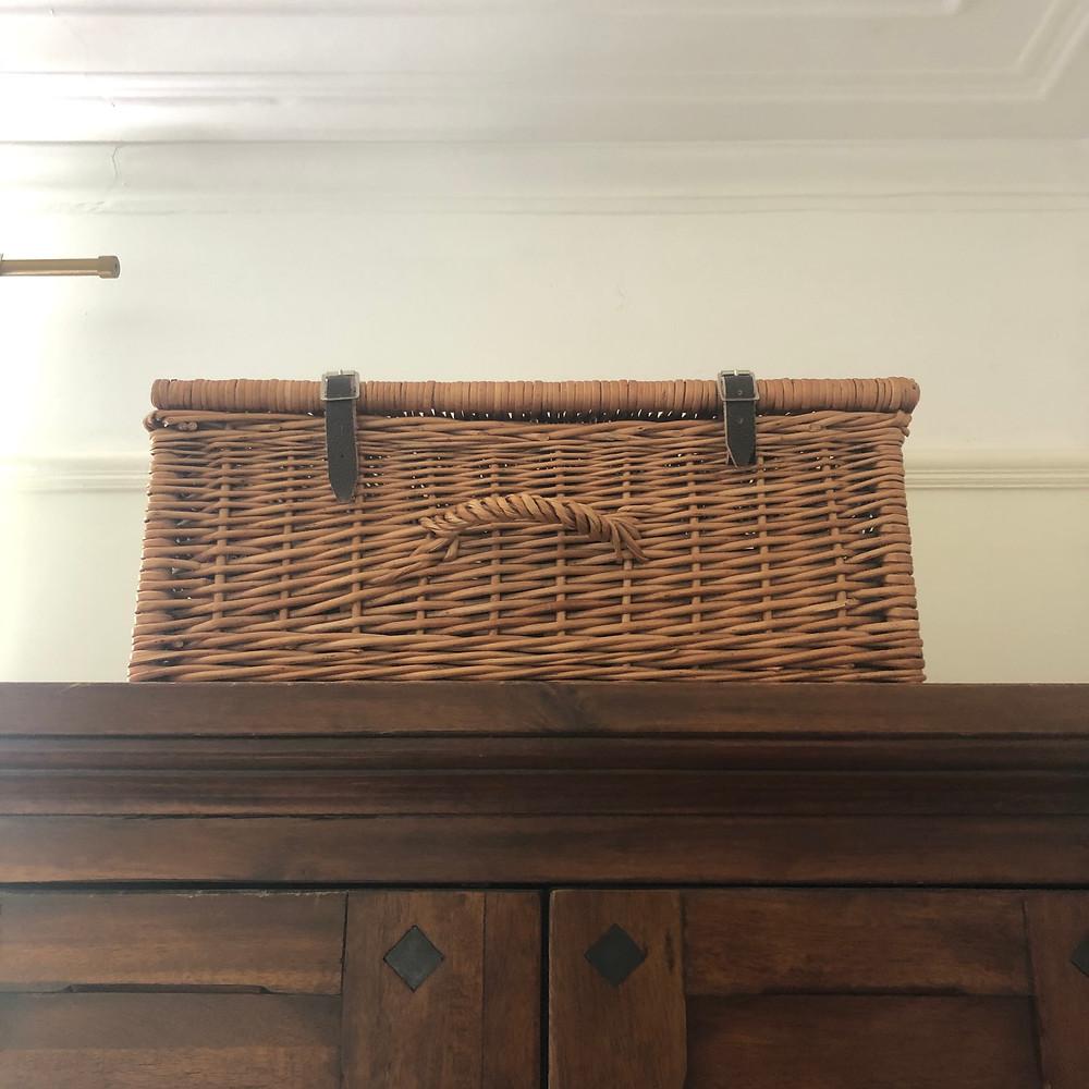Wicker hamper used for storage on top of wardrobe.