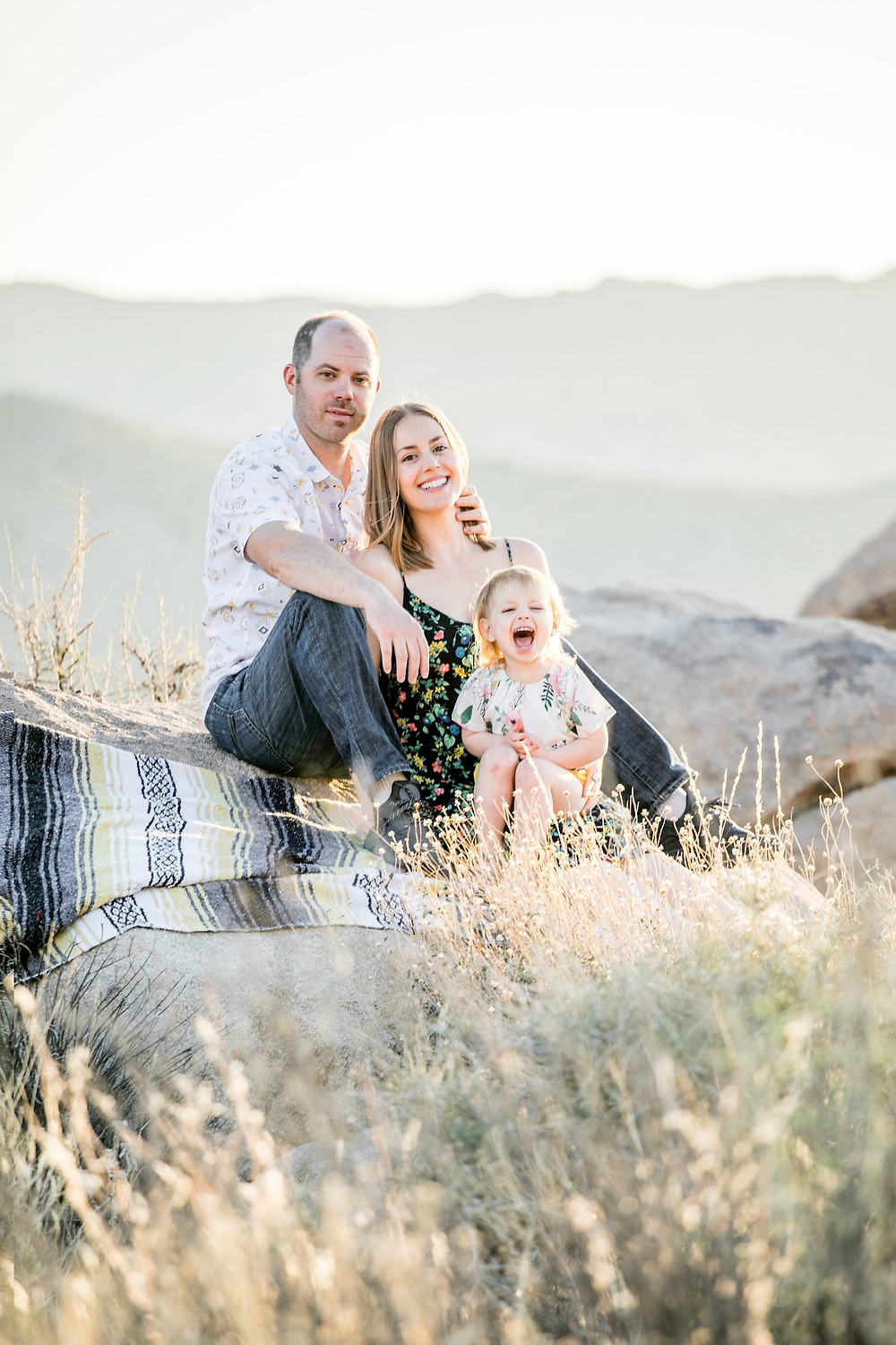 Family of three sitting on a blanket on top of a rock in Joshua Tree National Park.