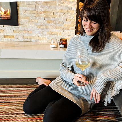 Brittney sitting near fireplace with glass of wine
