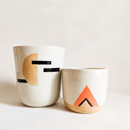 Two ceramic candles in golden, orange, and grey tones on a white back