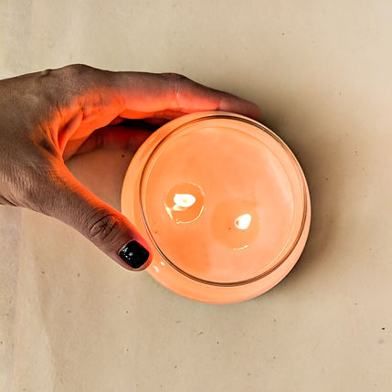 A hand holding a lit candle from above