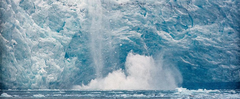 A portion of a glacier tumbles into the sea near Seward, Alaska