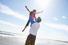 Father Throwing Daughter Into Air On Bea