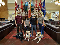 Four puppy raisers stand in front of a globe and some flags with a black lab and two yellow labs laying in front of them.
