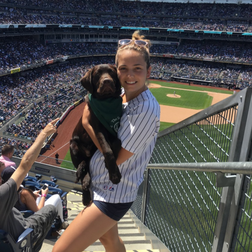 Brooke stand on the stairs of a baseball stadium with a chocolate lab in her arms.
