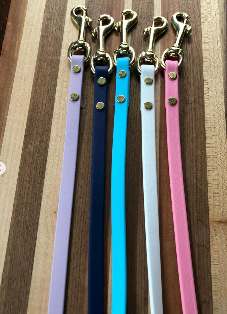 Five biothane leashes sit next to each other on a table. In focus are their clasps. Pictured is a lavender leash, a navy leash, a light blue leash, a white leash, and a pink leash.