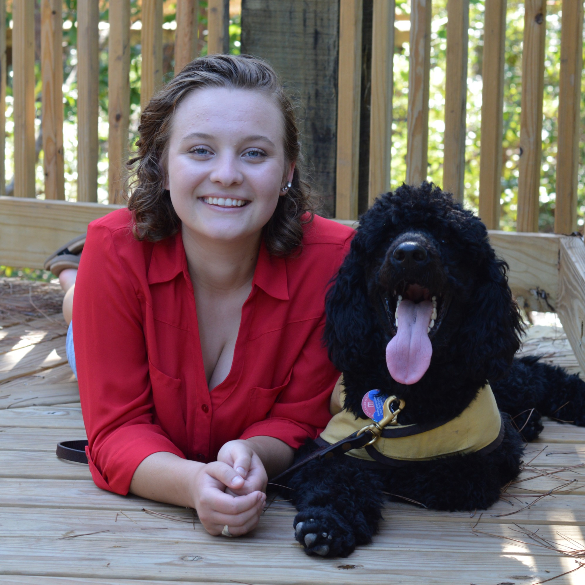 Julia lays on a deck next to a black standard poodle in a yellow vest.