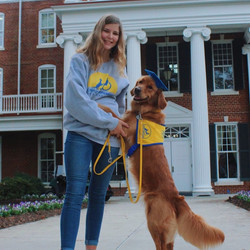 Ellen stands in front of a university building with a golden retriever in a yellow vest standing