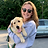 Jessica stands with a yellow lab in her arms.