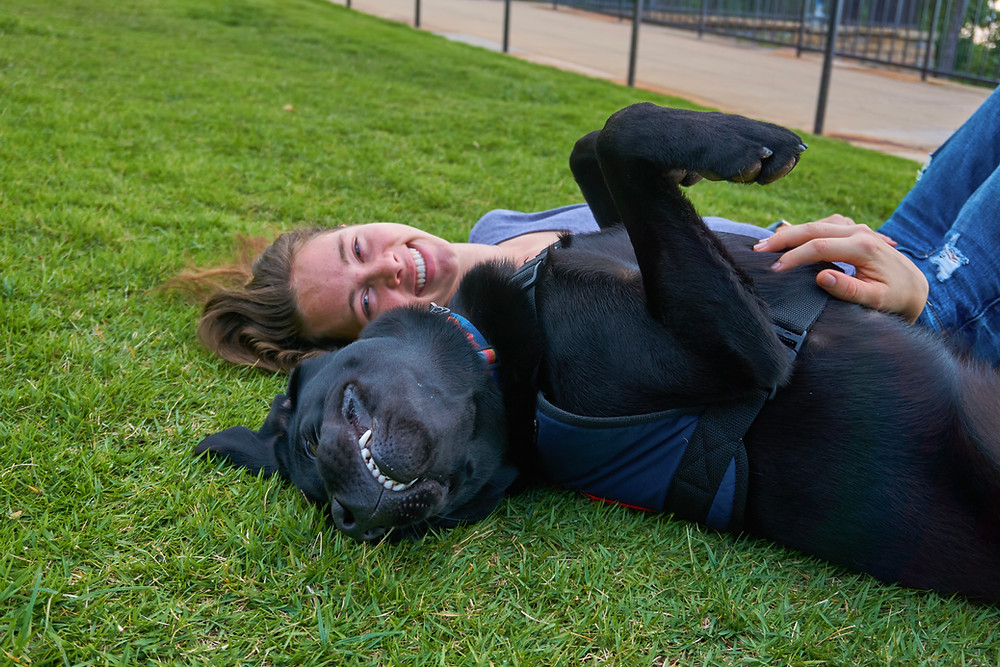 A girl lays in the grass with her puppy in training, a black lab who has their paws up and is giving a goofy grin.