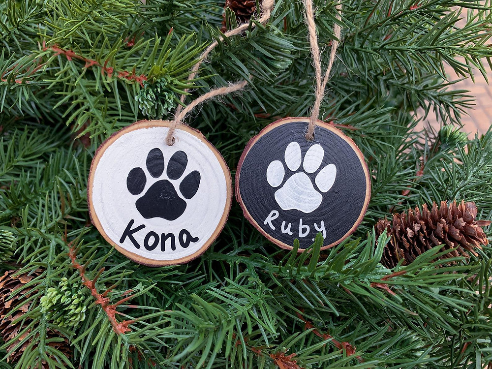 Two wood ornaments hanging from a Christmas tree. The left is painted white with a black paw print and the name Kona. The right is painted black with a white paw print and the name Ruby.