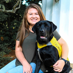 Camille sits next to a black lab in a yellow vest.