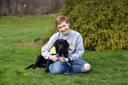 Nicole sits in a grassy field with a black lab in a yellow vest on her lap.