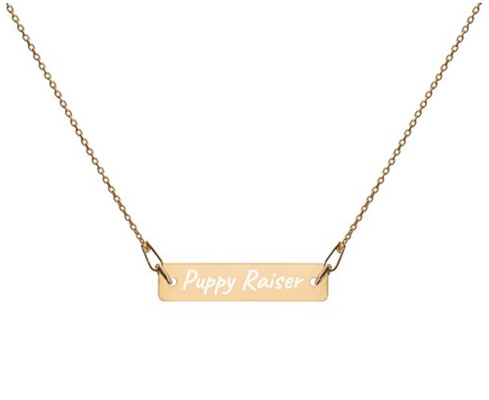A Gold bar necklace engraved with the words Puppy Raiser