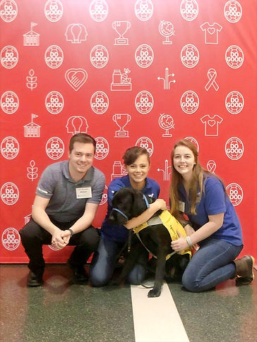 Scott, Vanessa, and Cate kneel in front of a red background. Vanessa is hugging a black lab in a yellow vest.