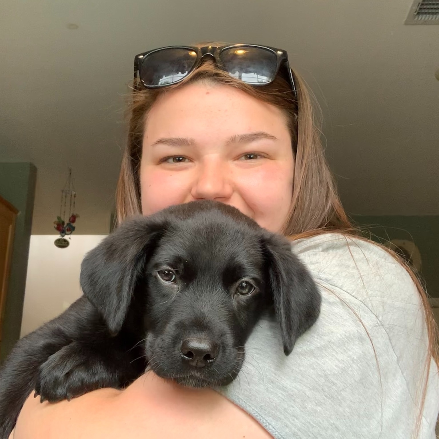 Christine holds a black lab puppy.
