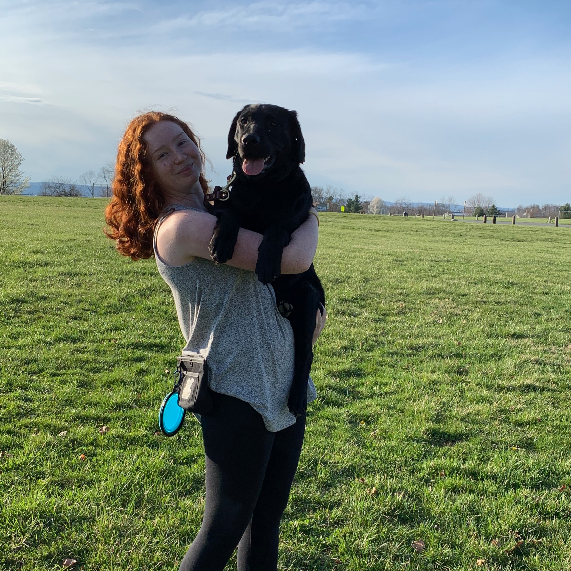 Kaitlyn stands in a grassy field and holds a black lab.