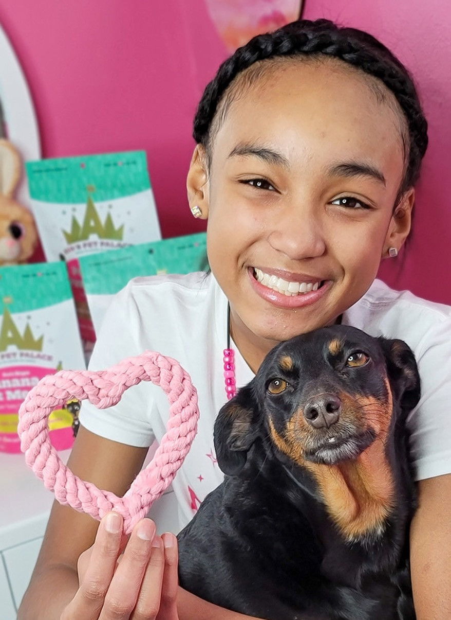 Ava, a 13 year old African American girl, smiles while holding her small Black and Tan dog.  In her right hand she holds a pink rope toy in the shape of a heart. Behind her are her branded dog treats.
