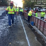 Saw cutting existing asphalt pavement on South Capitol St. SW for PCC half barrier footing.
