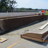 Curing Median Barrier Using Burlap at Overhead Sign Structures.
