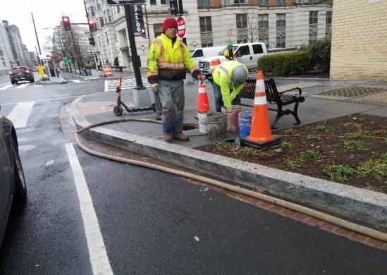 Omni Excavators working at NWC of 14th & N St parging pipe connections and draining catch basin