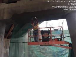 Finishing repaired shotcrete surfaces on bridge 1016 pier cap between columns 5 and 6