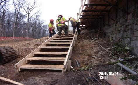 Constructing walkway on the eastern slope of Bridge 1016 Abutment B