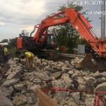 Removing rebars from demolished approach slab concrete rubble on bridge 1016 abutment B, left of baseline.
