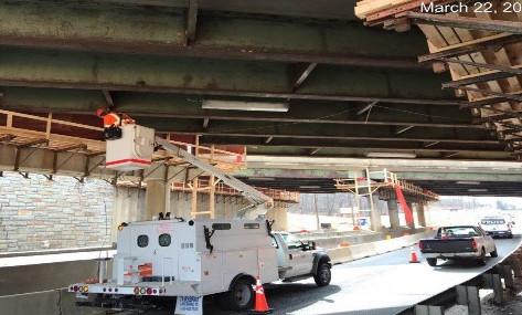 Jaxon Point installing temporary iunderbridge lighting.