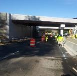Placing concrete in PCC half curb barrier cap.