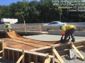 Placing wet burlap for curing concrete on Bridge 1016 abutment B appraoch slab, left of the baseline.