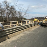 Installing temporary wooden handrails on Bridge 1017 parapet.