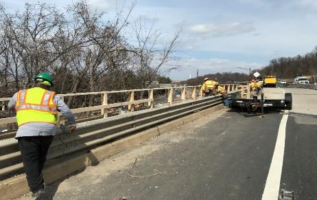 Installing temporary wooden handrails on Bridge 1017 parapet.