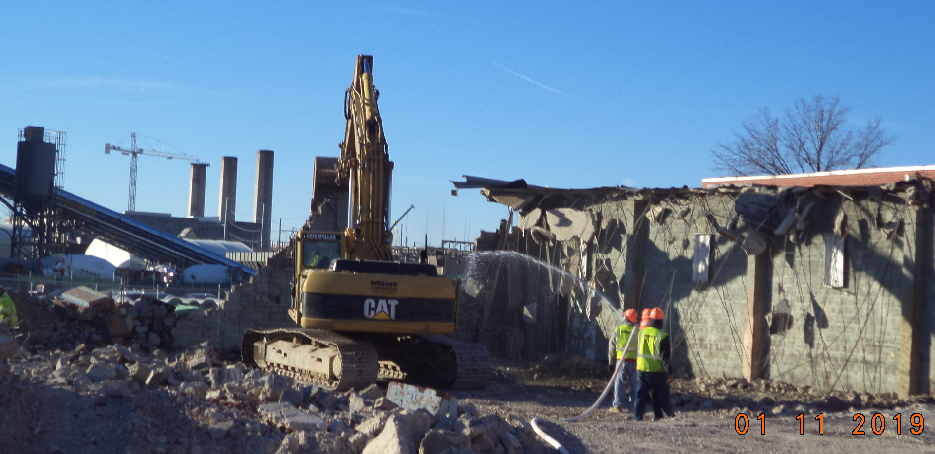 Demolition building using water hose to keep wet during demolition to prevent any dust particles from becoming airborne
