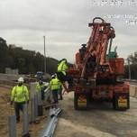 Installing Thrie beam approach transition on SB-295, NE corner of bridge 1017