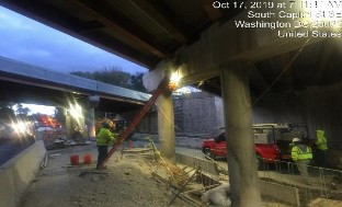 Masons plugging holes left by work platform brackets on pier cap
