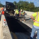 Placing asphalt wedging adjacent to steel plate over deck extension on bridge 1017 abutment A