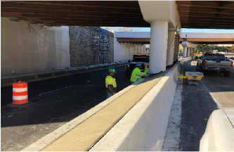 Finishing concrete placed in PCC half curb barrier cap.