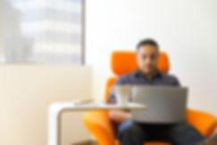 Canva - Man Sitting on Orange Sofa Chair