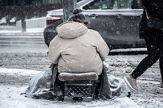 a homeless man sitting on the road side during winter