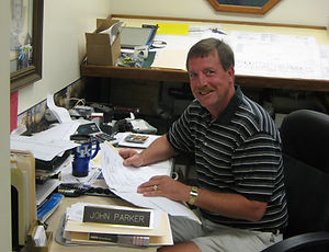 The owner, John Parker, sitting at his desk.