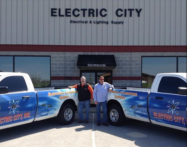 The two business owners smiling outside the shop with two identical trucks that have been painted with the company's logo.