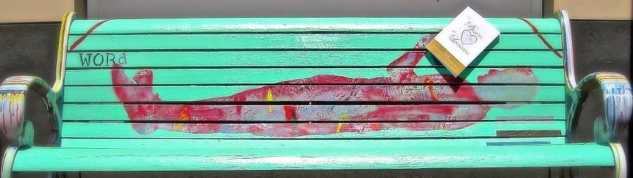 "The person resting on this painted bench is reading ""The Beauty of Listening"" poetry collection."