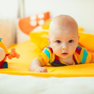 bebe-tumbado-en-una-cama-amarilla_1304-2